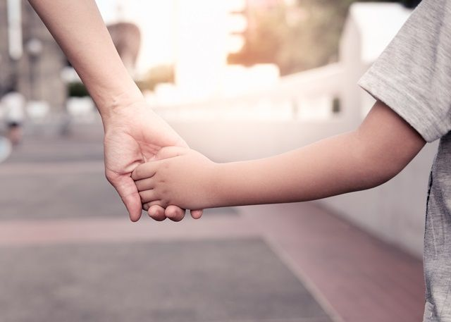 child and parent holding hands