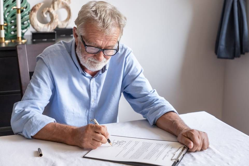Older man writing a document